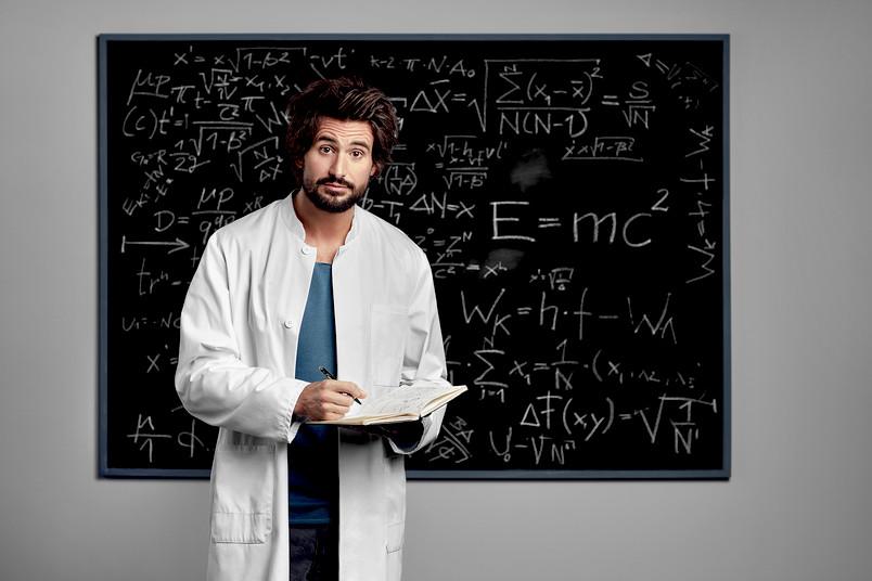 Tom Beck steht im weißen Kittel vor einer vollgeschriebenen Tafel.