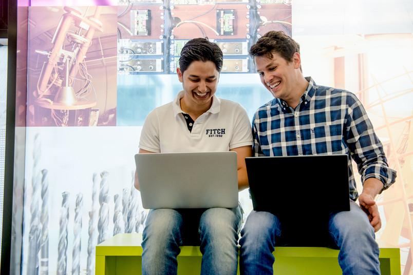 Zwei Männer lachen und haben ihre Laptops auf dem Schoß