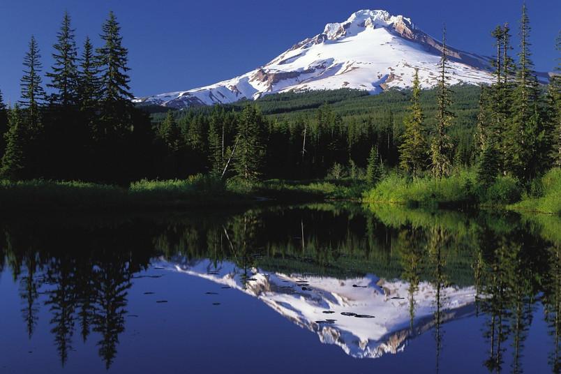Schneebedeckter Berg, der sich in einem See spiegelt