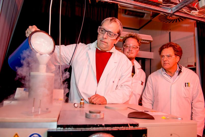 Drei Männer in weißem Kittel, einer füllt flüssigen Stickstoff in ein Messgerät.