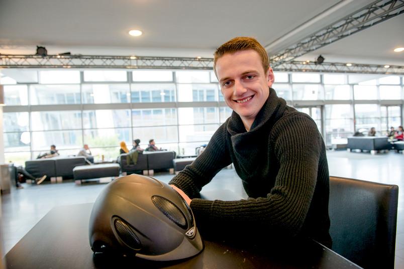 Ein junger Mann sitzt in der Kaffeebar. Auf dem Tisch vor ihm liegt ein Reithelm.