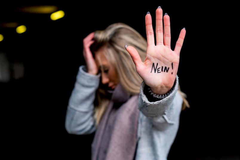 """Eine Frau zeigt ihre Handinnenfläche, auf der """"Nein"""" steht."""