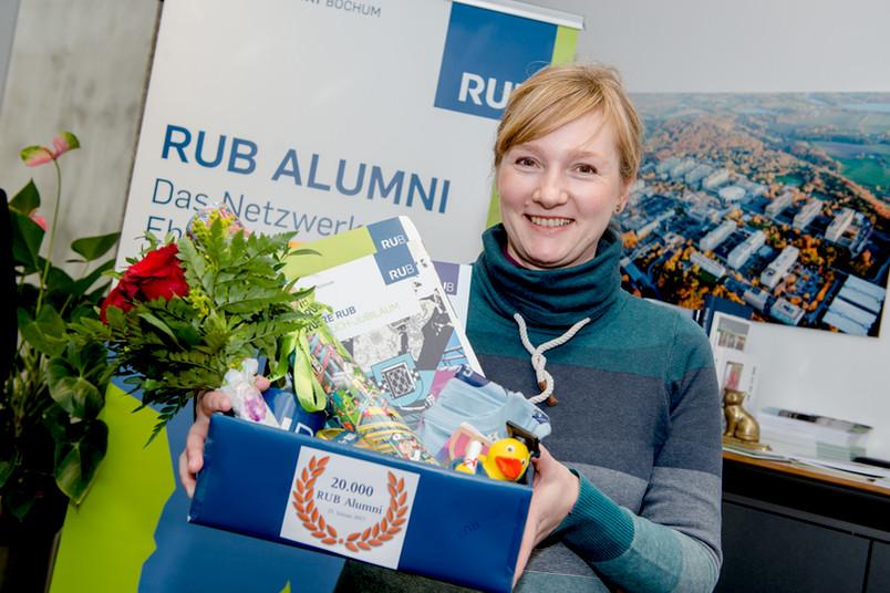 Porträt einer etwa 40-jährigen Frau mit Blumen und Geschenken in der Hand