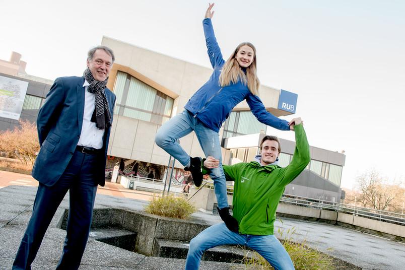 Rektor Schölmerich steht neben den Eiskunstläufern, die auf dem Campus eine artistische Hebefigur machen.
