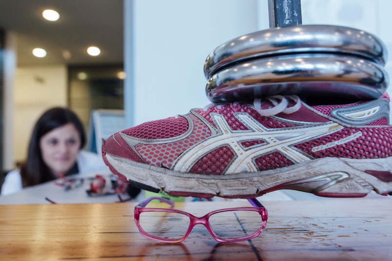 Eine Schulsportbrille wird getestet, indem sie unter ein Gewicht gelegt wird, dem sie standhalten soll.