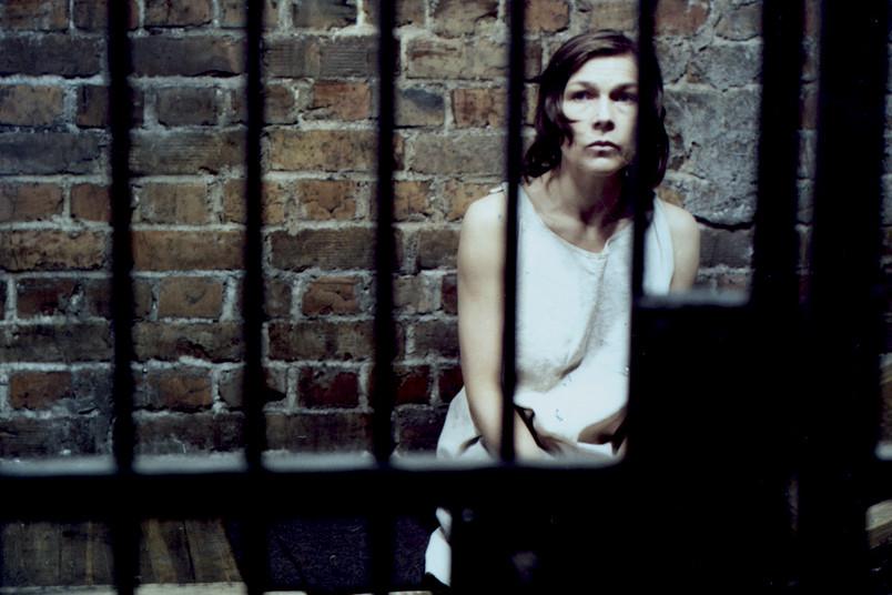 Filmszene: Junge Frau sitzt in einer Gefängniszelle