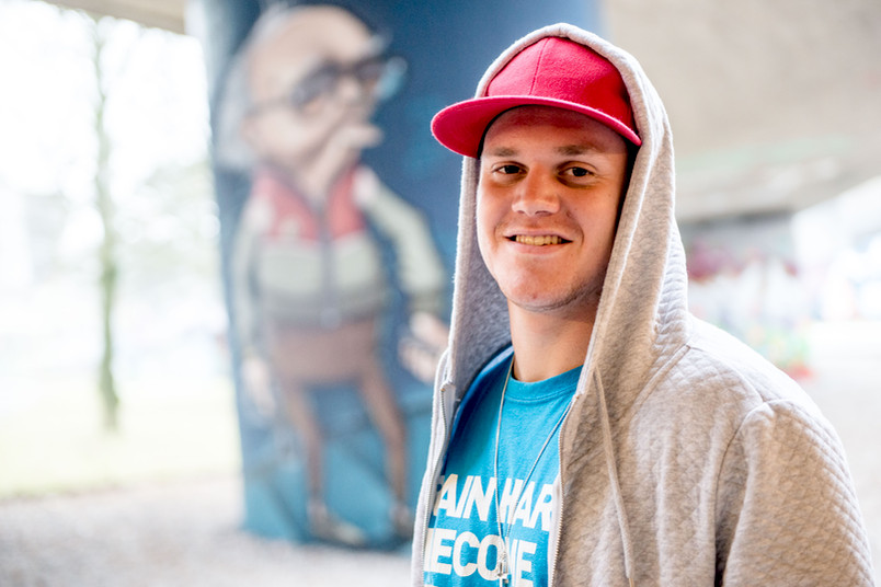 Ein junger Mann mit Kapuze über der Cappie steht vor einem Graffiti