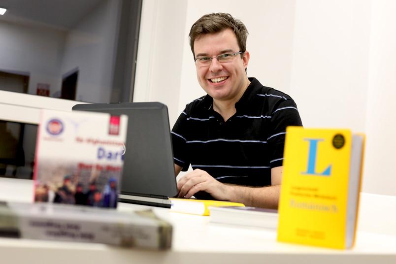 Student sitzt mit Wörterbüchern am Laptop.