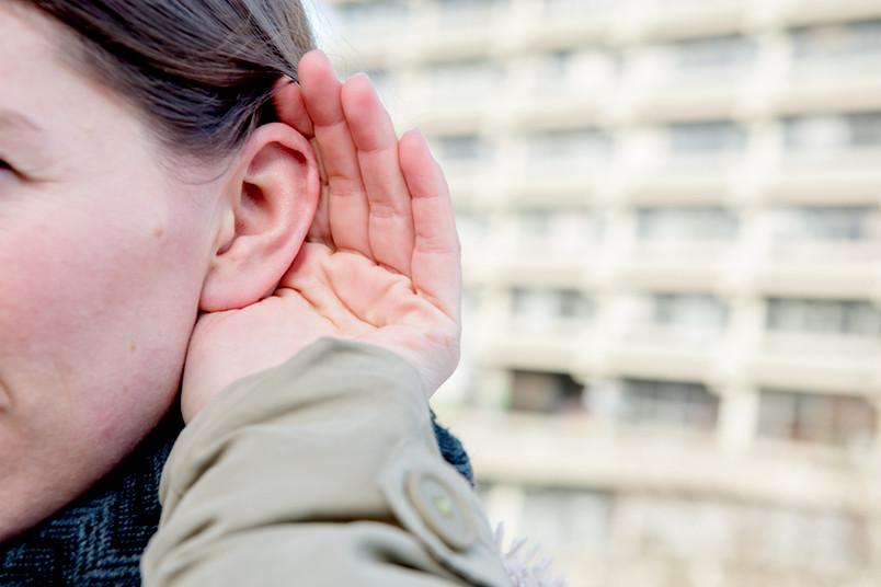 Ein Hand formt eine Muschel hinter einem Ohr.
