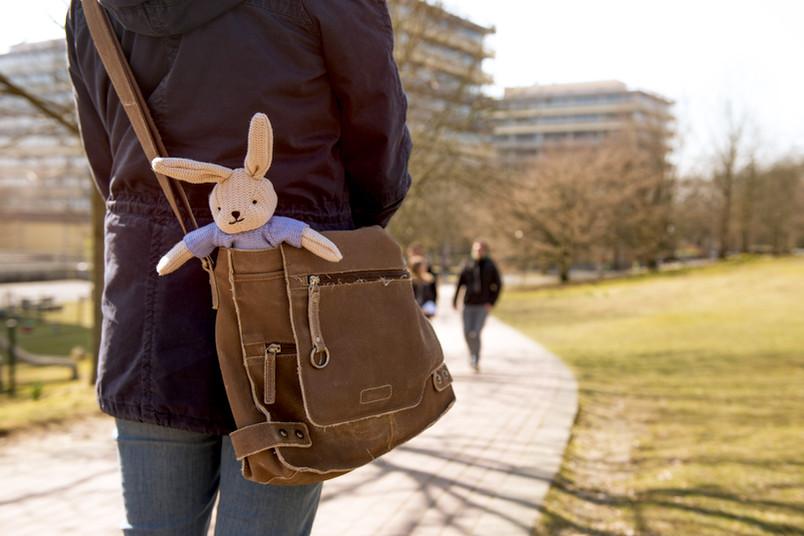 Studentin von hinten, offenbar auf dem Weg zur Vorlesung, aus ihrer Tasche lugt ein Stoffhase hervor