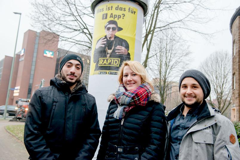 Dozentin Katharina Friedrichs mit zwei Studenten vor dem Plakat an einer Litfaßsäule
