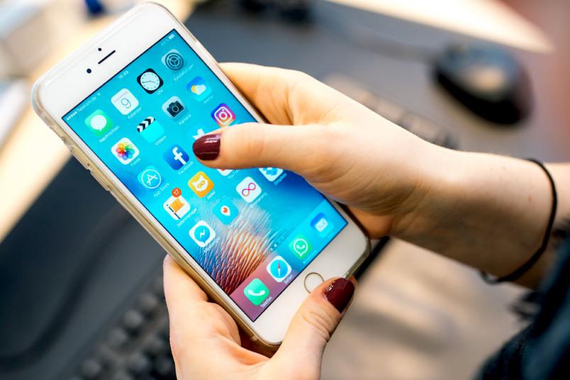 Daumen bewegen sich über den Bildschirm eines Smartphones.