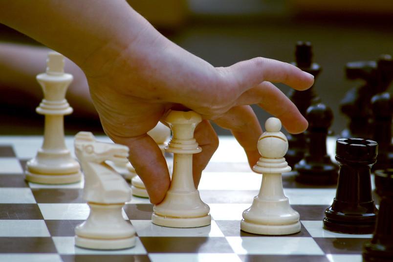 Hand über einem Schachbrett