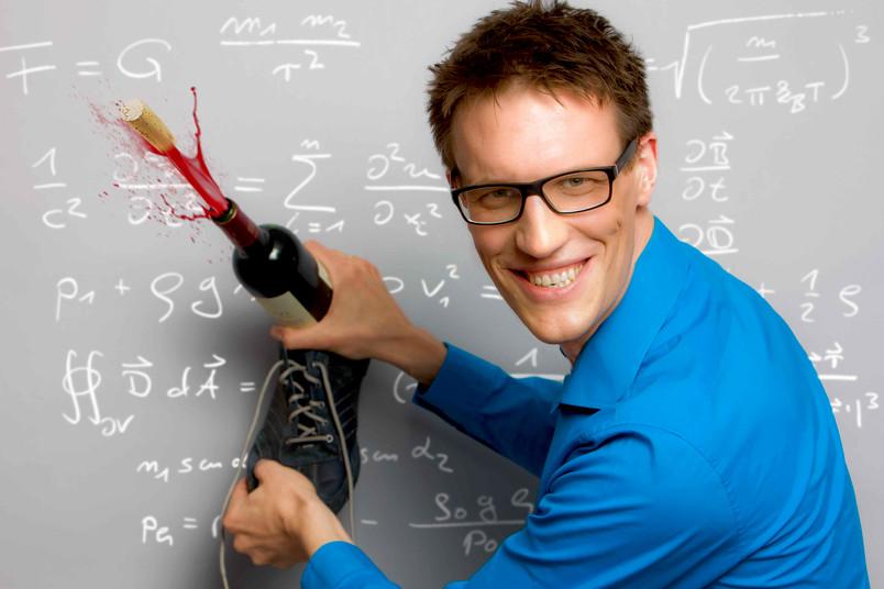 Witziges Porträt eines 30-jährigen Mannes vor einer Tafel, mit Schuh und Weinflasche