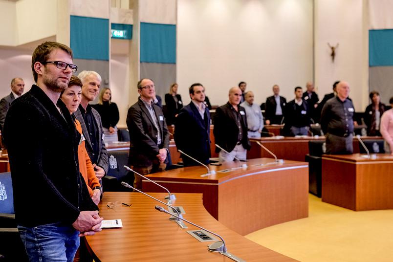 In einem Plenum stehen Menschen.