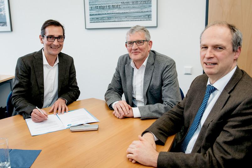 Drei Männer sitzen an einem Tisch.