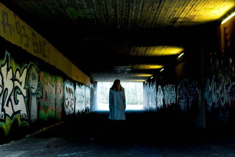 Eine Frau ist von hinten in einem dunklen Fußgängertunnel zu sehen.