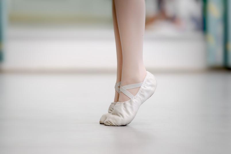 Beine einer Balletttänzerin, die auf Zehenspitzen steht