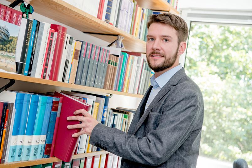 Wissenschaftler holt Buch aus einem Bücherregal.