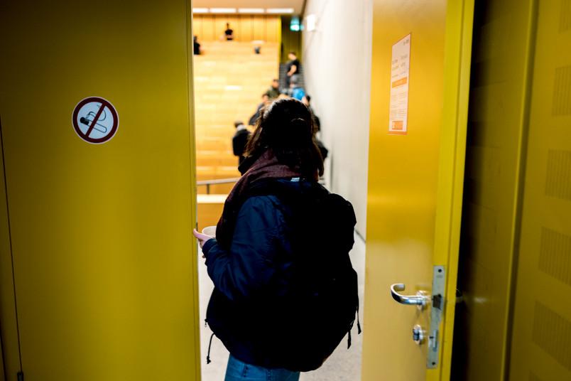 Eine Studentin steht in der offenen Tür eines Hörsaals.