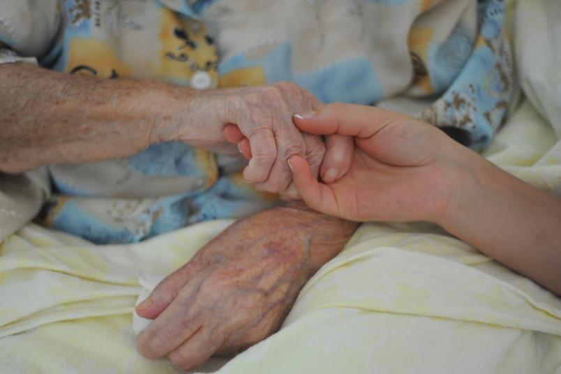junge Hände halten die Hände einer alten Frau.