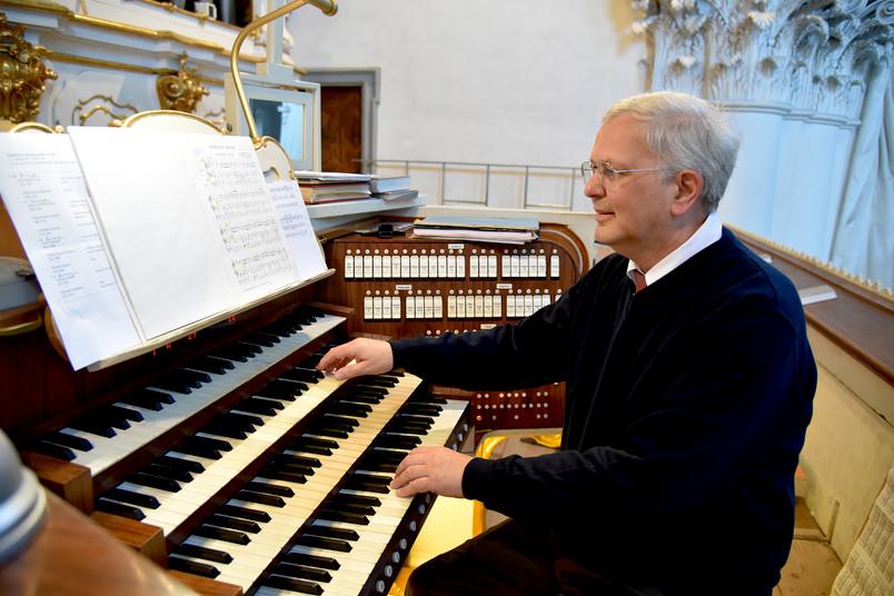 Porträt eines etwa 60-jährigen Mannes, der Orgel spielt