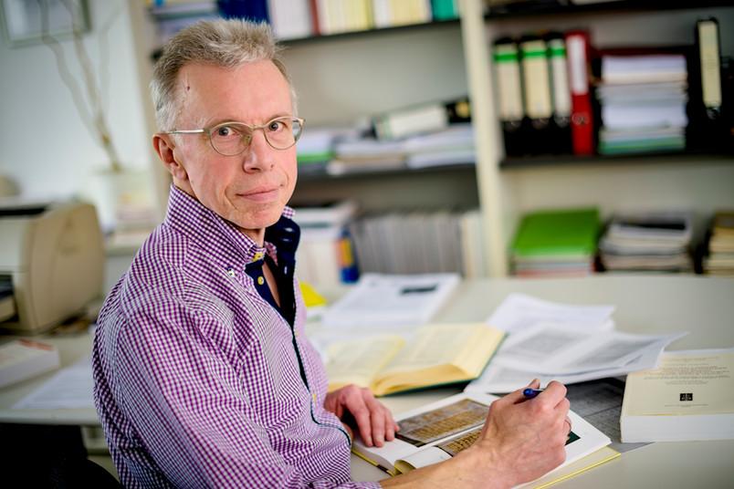 Wissenschaftler sitzt mit einem Buch an einem Schreibtisch.