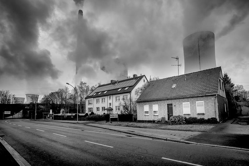 Schwarz-weiß-Aufnahme einer tristen Straße im Industriequalm
