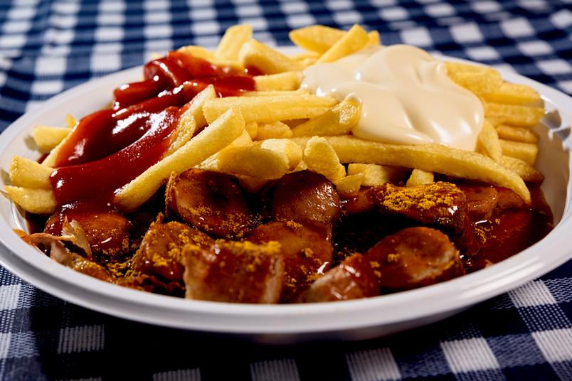 Teller mit Currywurst und Pommes frites