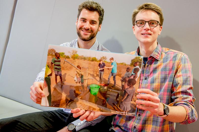 Zwei Männer halten im Sitzen ein Bilderbuch.