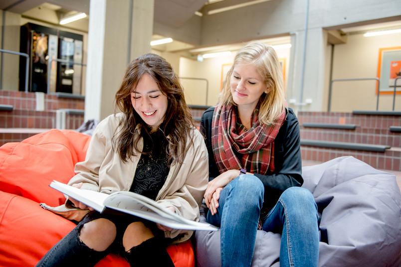 Zwei junge Frauen sitzen auf Kissen auf dem Boden und schauen lachend in ein Buch.