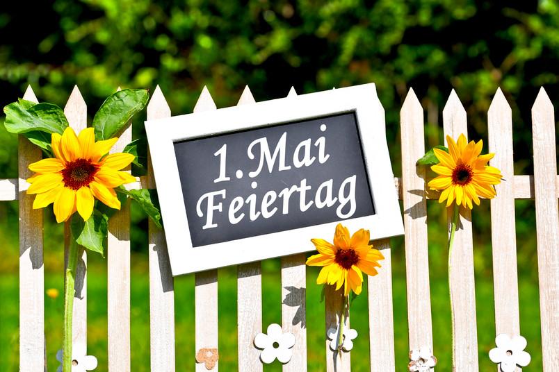 """Bretterzaun mit Tafel, auf der """"1. Mai"""" steht"""