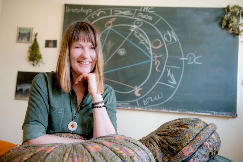 Frau vor Tafel, auf der ein Horoskopkreis zu sehen ist.