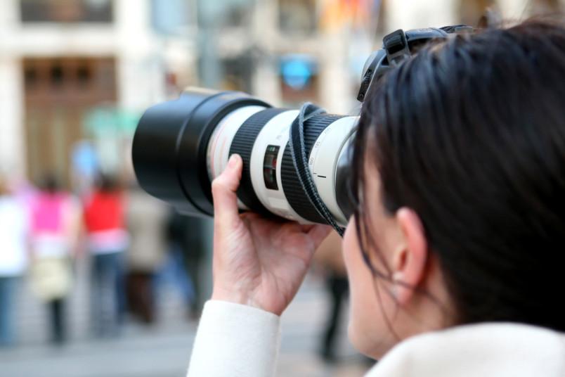 Frau mit Fotoapparat und langem Objektiv