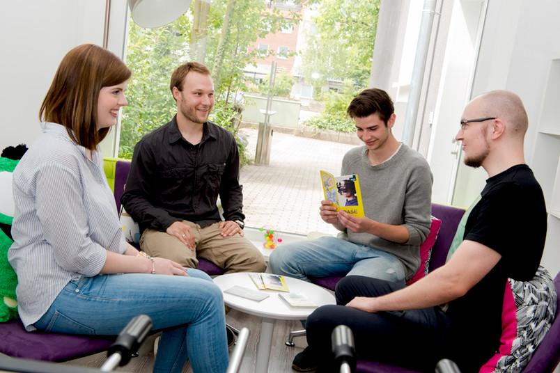 Vier Studierende sitzen in einem Stuhlkreis und unterhalten sich lachend.