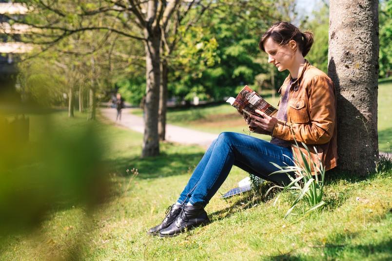 Porträt einer etwa 30-jährigen Frau, die auf der Wiese sitzt und ein Buch liest