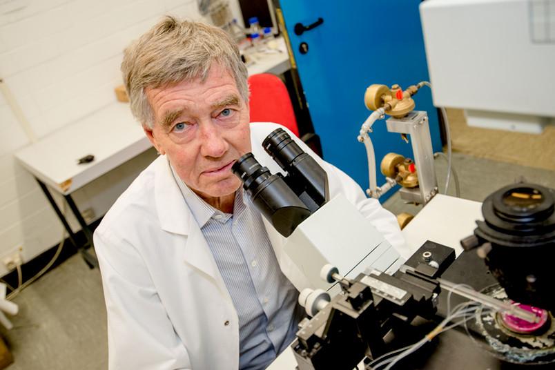 Mann sitzt hinter einem Mikroskop.