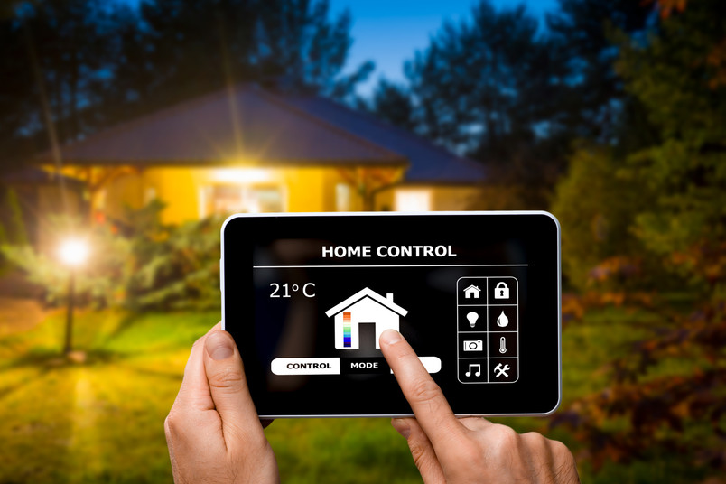 Eine Hand steuert mit einem Tablet Technik in einem Haus im Hintergrund.