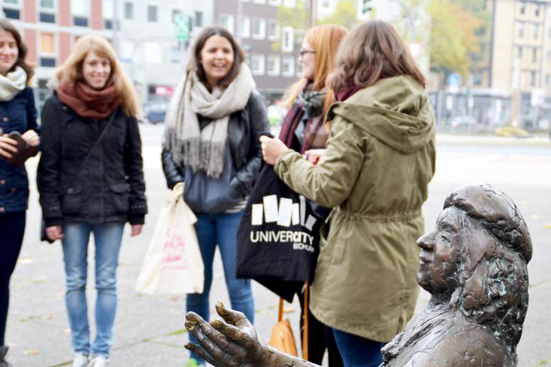 Junge Menschen stehen neben einer Statue zusammen