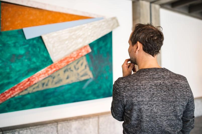 Mann betrachtet ein Kunstwerk.