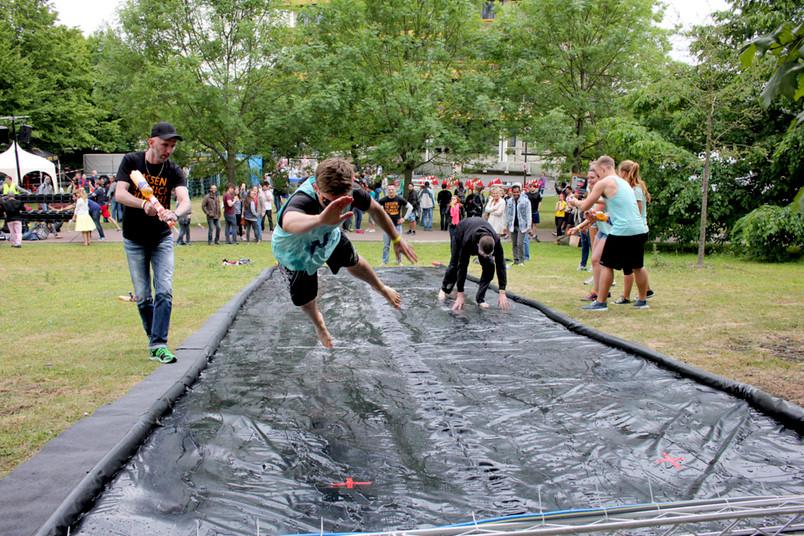 Studierende bei einem Spaßwettbewerb springen über eine schwarze Folie.