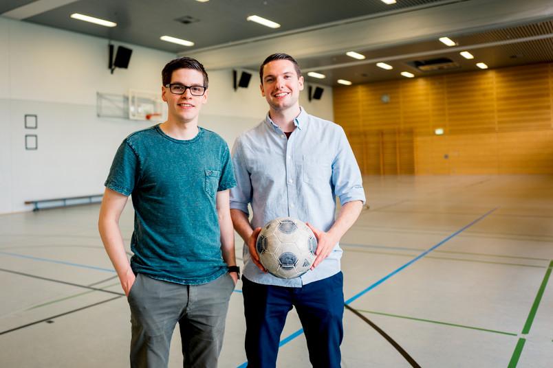 Zwei junge Männer mit Fußball in einer Sporthalle