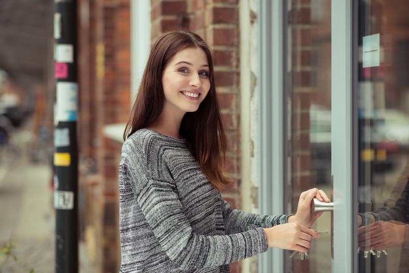 Junge Frau schließt eine Tür auf.