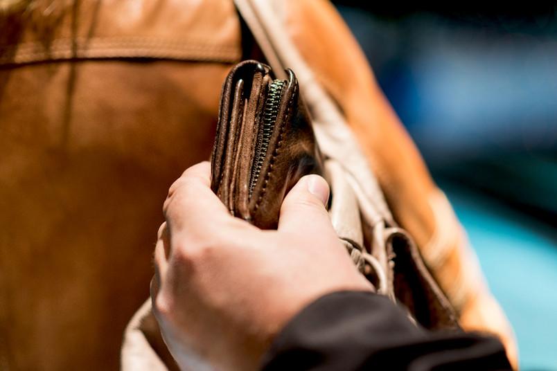 Hand nimmt Portemonnaie aus der Tasche