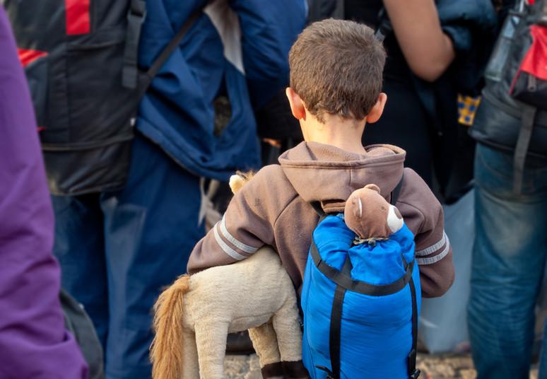 Kleiner Junge von hinten mit Stofftier in Menschenmasse