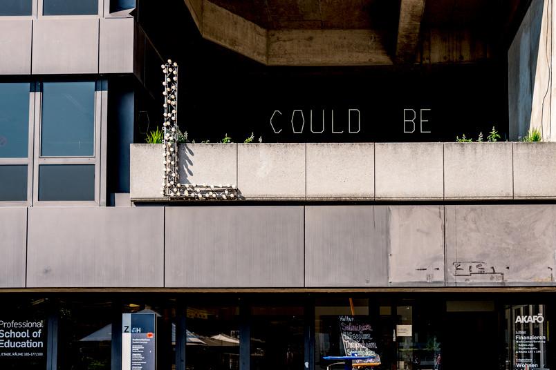 """Schriftzug """"L COULD BE"""" aus Glühbirnen an einem Gebäude"""