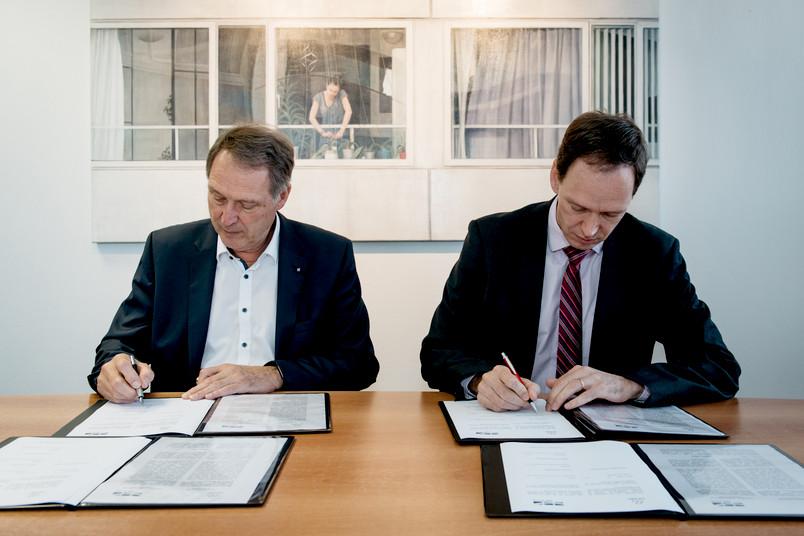 Zwei Männer unterzeichnen Verträge