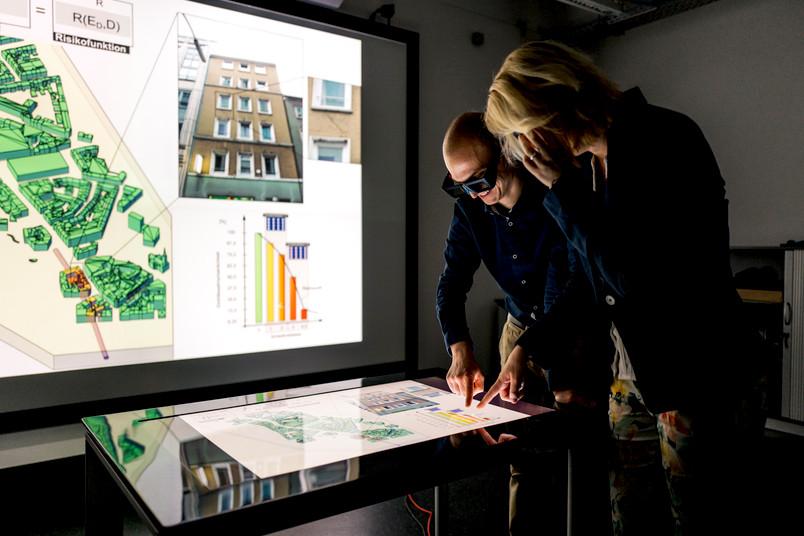 Ein Mann und eine Frau schauen auf einen großen Touchscreen
