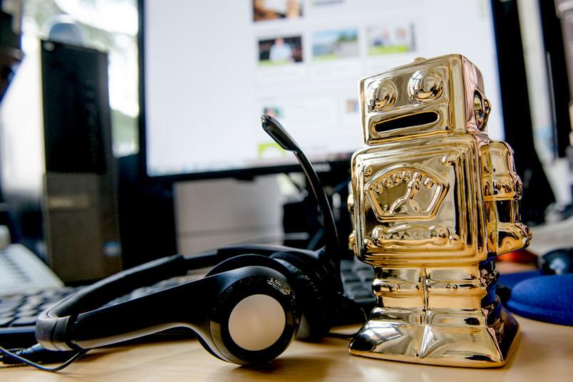 Telefonheadset und ein goldender Roboter nebeneinander