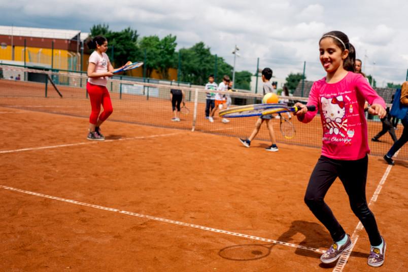 Mädchen jongliert Tennisball auf einem Schläger.